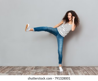 Portrait of strong young female with curly brown hair kicking invisible opponent, punching with leg over grey wall