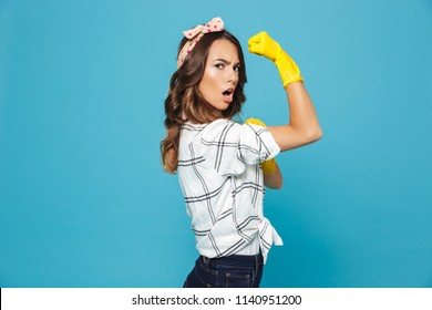 Portrait of strong young woman 20s showing bicep while wearing yellow rubber gloves for hands protection during cleaning isolated over blue background