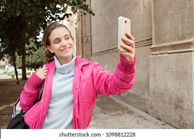 Portrait of student in college campus carrying backpack using smart phone to take selfies photos, networking smiling outdoors. Young woman with technology photo device, leisure recreation lifestyle.