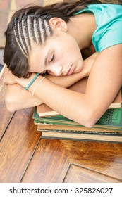portrait of student girl asleep on a stack of books at the library