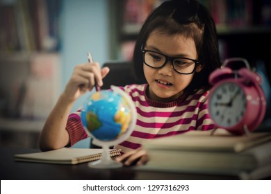Portrait of a student girl studying at library with world globe looking map wold
