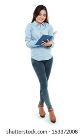 Portrait of student holding book and writing isolated over white background