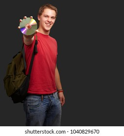 Portrait Of A Student Holding A Compact Disk On Black Background