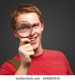 Portrait Of A Student Looking Through Magnifying Glass On  Black Background