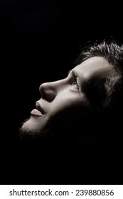Portrait of a student,man side profile looking up lighted on a half face isolated on black background.Concept hope,freedom,.Face expression.