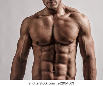 Portrait in studio of muscular malebody. Isolated on grey background.