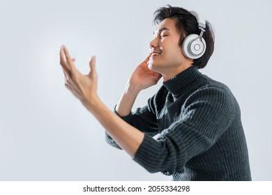 portrait studio music lyric concept yound smart asian artist wear  sweater listen headphone enjoy music audio in dance with happiness mood positive movement eye close white background