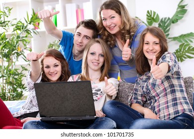 Portrait of study group with laptop, showing thumbs up
