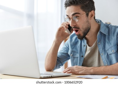 Portrait of stunned brunet male freelancer looks with stupefied expression into laptop computer, talks via smart phone, being pleasant astonished to recieve high money award, shares news with friend
