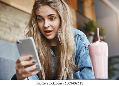 Portrait of stunned and impressed attractive blond woman in denim jacket, sitting in cafe and drinking strawberry cocktail, holding smartphone and dropping jaw from show, staring at gadget screen