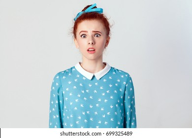 Portrait of stunned redhead young girl looking at the camera with shocked expression, mouth wide open, surprised with unexpected news. Isolated studio shot on gray background.