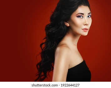 Portrait of stunning asian woman with a beautiful curly hair and make-up over red background