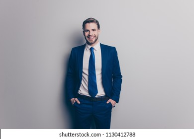 Portrait of stunning, attractive, sexy, smiling, manly man in blue suit with tie with stubble, holding two hands in pockets of pants, looking ta camera, isolated on grey background