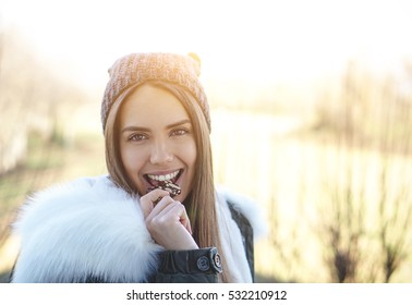 Portrait of a stunning and cheerful girl eating chocolate outside on a cold winter day - Smiling girl with a hat looking the camera