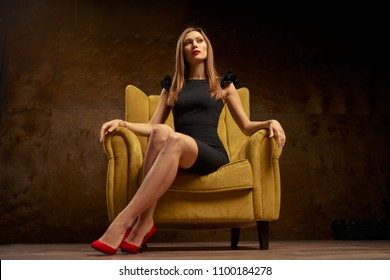 Portrait of a stunning fashionable model sitting in a chair. Business, elegant businesswoman.