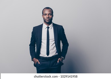 Portrait of stunning, manly, brutal man in black tux, tuxedo with white shirt and tie, holding two hands in pockets of pants, looking at camera, going for meeting, isolated on grey background