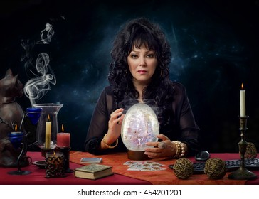 Portrait of stunning mature crystal gazer sitting at the desk surrounded by burning candles. Black haired female fortuneteller is scrying with big crystal egg and looks intently at the camera