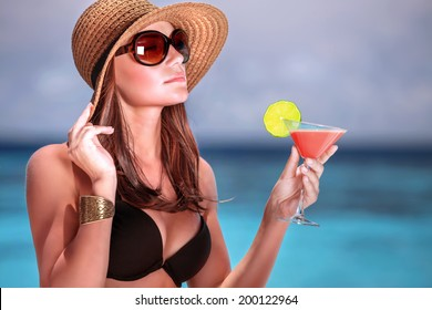 Portrait of stunning woman wearing stylish beach hat and sunglasses drinking cocktail outdoors, summer vacation on Maldives resort