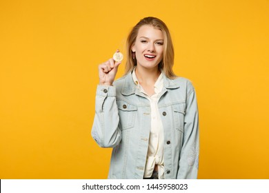 Portrait of stunning young woman in denim casual clothes looking camera holding bitcoin, future currency isolated on yellow orange background in studio. People lifestyle concept. Mock up copy space