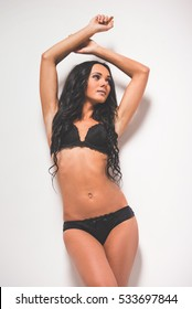 Portrait of a stunning young woman posing in black lingerie on grey background