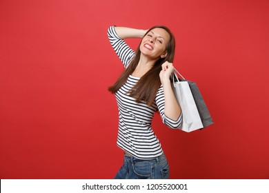 Portrait of stunning young woman in striped clothes holding packages bags with purchases after shopping isolated on red wall background. People sincere emotions, lifestyle concept. Mock up copy space