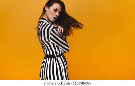 Portrait of stunning young woman wearing striped dress standing against orange background. Beautiful female model with vivid makeup posing in studio.