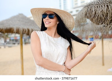 Portrait of stunningly beautiful young woman in a white dress and sunglasses. Gorgeous female on beach outdoors background