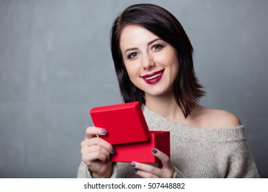 Portrait of a style brunette woman with little red gift box on grey background