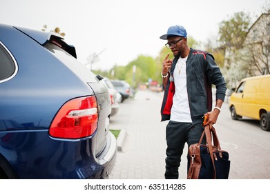 Portrait of stylish african american man on sportswear, cap and glasses walking with handbag and open car trunk. Black men model street fashion.
