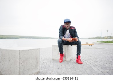 Portrait of stylish african american man on sportswear, cap and glasses sitting at stone cube with phone at hand. Black men model street fashion.
