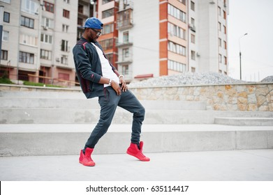 Portrait of stylish african american man on sportswear, cap and glasses. Black men model street fashion, dancing hip hop.