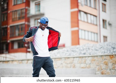 Portrait of stylish african american man on sportswear, cap and glasses. Black men model street fashion.