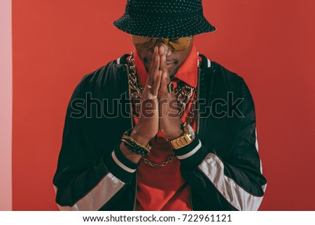 57c30828721 portrait of stylish african american man wearing jewellery and hat standing  in studio