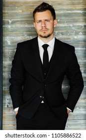 portrait of stylish athletic ofiice man in a business owner costume vest. background of a interior cafe loft. stands on the background of a wooden wall. Hands in pockets.