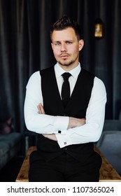 portrait of stylish athletic ofiice man in a business owner costume vest. background of a interior cafe loft. Sitting on the wooden table. He crossed his arms over his chest.