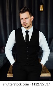 portrait of stylish athletic ofiice man in a business owner costume vest. background of a interior cafe loft. Sitting on the wooden table. Hands in pockets.