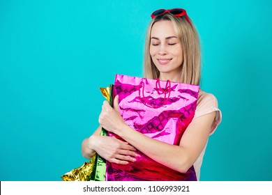 portrait of a stylish and attractive shopaholic female person smiling and hugs a lot of shopping bags on a blue background in the studio. concept of shopaholism and sales