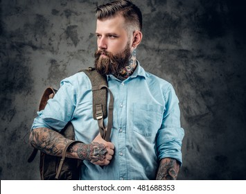 Portrait of stylish beard, male with tattoos on his arms and neck with backpack on his back.