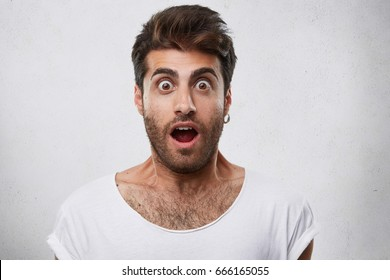 Portrait of stylish bearded guy having trendy hairstyle wearing earring and white T-shirt looking with his eyes popped out and opened mouth having shock and scared look. People and emotions concept