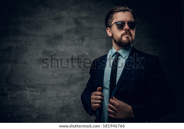 Portrait of stylish bearded hipster male dressed in a jacket, bow tie and sunglasses.