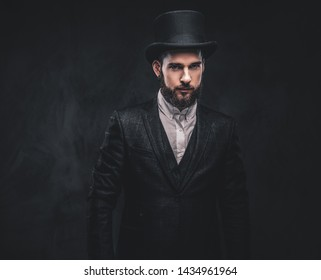 Portrait of a stylish bearded male in an elegant suit and cylinder hat, looking at a camera over dark background.