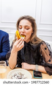 Portrait of a stylish beautiful woman eating banana chifles with fake squid noodles and beluga caviar at the dinner party