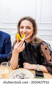 Portrait of a stylish beautiful woman eating at private dinner party at home. Woman eating banana chifles with fake squid noodles and beluga caviar.