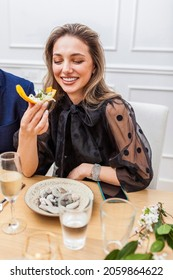Portrait of a stylish beautiful woman eating a canape at private dinner party at home. Woman eating banana chifles with fake squid noodles and beluga caviar.