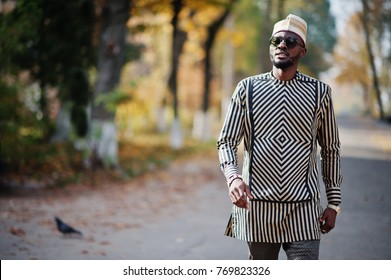 Portrait of stylish black african american man at hat and sunglasses against sunny autumn fall background. Rich people in africa at traditional dress.