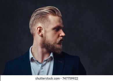 Portrait of stylish blond bearded male dressed in a suit over grey background.