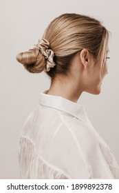 Portrait of stylish blonde with hair collected in silk beige scrunchie, wearing white blouse and posing against light background. Beauty and tenderness concept