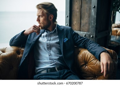 portrait of stylish blonde handsome groom sitting on the leather chair and looking at the sea view