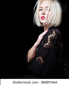 Portrait of a stylish blonde with short hair in a black dress on a black background