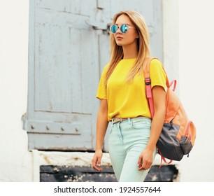 Porträt einer stylischen blonden jungen Frau, die in einer Stadt auftritt